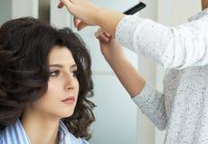 手的特写镜头梳在顾客的发式专家的视图和梳子一种新的发型在发廊朝向 免版税库存照片
