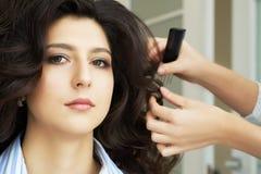 手的特写镜头梳在顾客的发式专家的视图和梳子一种新的发型在发廊朝向 库存图片