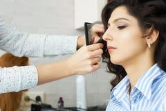 手的特写镜头梳在顾客的发式专家的视图和梳子一种新的发型在发廊朝向 免版税图库摄影