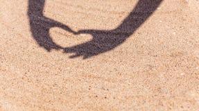 从手的阴影以在沙子的心脏的形式在与空间的海滩文本的 海上旅行和假日 免版税库存图片