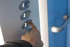 手紧迫在电梯的二楼按钮 库存图片