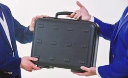 手给交换或提议贿款的公文包 商业转移概念 男性手举行公文包 案件移交  免版税库存照片