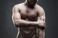 手肘痛苦 肌肉机体的男 摆在灰色背景的英俊的爱好健美者 演播室射击的低调关闭 库存图片