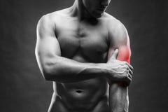 手肘痛苦 肌肉机体的男 摆在灰色背景的英俊的爱好健美者 免版税库存照片