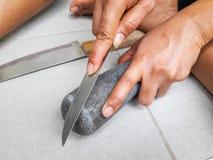 手藏品削尖刀子和磨刀石 免版税图库摄影