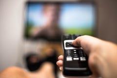 手藏品用途遥控和观看的电视在现代一个五颜六色的平面式屏幕的议院里 免版税图库摄影
