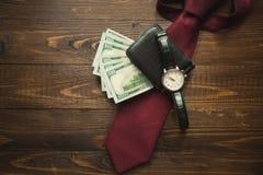 手表、金钱在钱包和红色领带在黑暗的木backgro 免版税库存图片