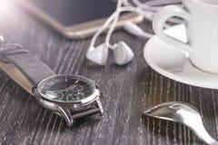 手表和手机有耳机和一杯咖啡的在一张黑暗的木桌上 免版税库存照片