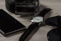 手表,皮带,出售电话,在灰色木头的黑太阳镜 免版税库存图片