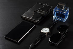 手表,笔记本,出售电话,人香水,在黑色的太阳镜 免版税库存照片