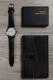手表,笔记本,在灰色木背景的名片持有人 免版税库存图片