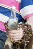 手被束缚到一个瓶酒精,坐在椅子的一个人 免版税库存照片