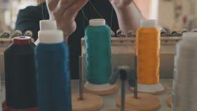 手裁缝调整与红色和黄色螺纹的卷 影视素材