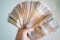 手计数thousansds泰铢金钱 人的计数的泰国钞票,richman计数和拿着一百泰铢票据的关闭 图库摄影