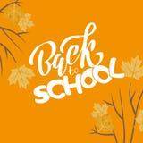 手速写了白色回到letering的学校课文在橙色背景和枫叶在分支 对商标,横幅,飞行物 皇族释放例证