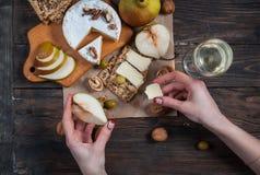 手采取乳酪和梨和平从桌用食物 免版税库存图片