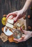 手采取乳酪和玻璃酒和平从桌的用食物 库存照片