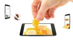 手采取橘子果酱以超出智能手机的屏幕范围的橙色切片的形式,隔绝在白色背景 库存照片