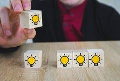 手采摘了与黄灯电灯泡标志的木立方体在木桌上 新的想法,创新和解答概念 库存图片