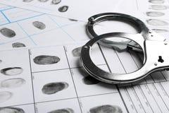手铐和指纹纪录板料 刑事调查 图库摄影