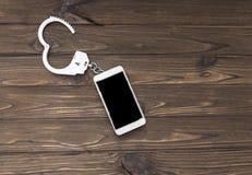手铐和智能手机在木背景 库存照片