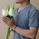 手铐和莲花的年轻人在手中 免版税库存照片