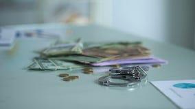 手铐和金钱在桌,贿赂处罚,财务管理系统上 股票视频