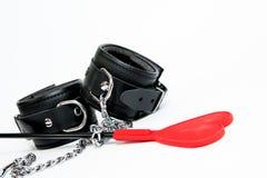 黑手铐和鞭打的鞭子 免版税库存照片