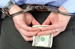 手铐的人拿着在他的棕榈的金钱在他的后  图库摄影