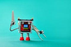 手锯钳子在深蓝纸背景的军人机器人 与金属修理硬件的滑稽的玩具杂物工字符 免版税库存照片