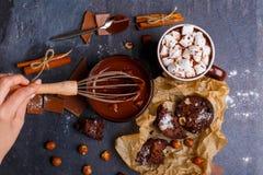 手阻碍与三角背心熔化了巧克力用榛子 免版税图库摄影
