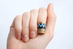 手,在她的手指的一个顶针 库存图片