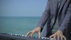 手,音乐家的手指数字式钢琴的 年轻人执行在天蓝色的海岸、海滩或者码头的witm合成器 男 股票视频
