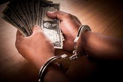 手年轻人在扣上手铐的举行金钱 库存照片