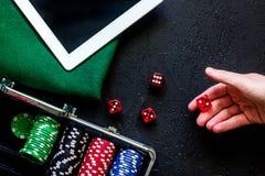 手滚动模子 啤牌在一种金属案件、绿色赌博的布料和片剂设置了在一个灰色台式视图 库存照片