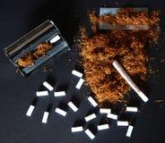 手滚动的香烟和烟草 库存照片