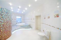 洗手间和极可意浴缸在宽敞白色卫生间里 库存图片