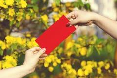 手给在红色信封- ang战俘或红色小包的金钱对一些 免版税库存照片
