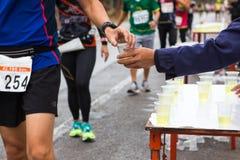 手给矿泉水未认出的赛跑者 免版税图库摄影
