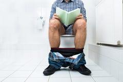 洗手间阅读书的人 免版税图库摄影