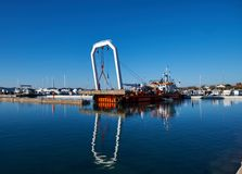 扎达尔,克罗地亚,2018年11月29日 支持在被拆毁和替换的具体码头的驳船举的零件的起重机 库存照片