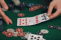 扑克牌游戏在人在选材台上的` s手上 免版税库存照片