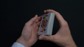 扑克牌游戏-拖曳卡片 人shuffing卡片的` s手 关闭 人拖曳纸牌的` s手 经销商` s手 免版税库存图片