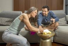 打一个电子游戏的阿拉伯人,当妇女在他附近时清洗 免版税库存图片