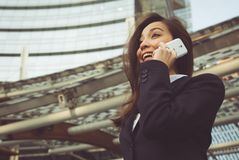 打一个电话在办公室外的女商人 免版税库存图片