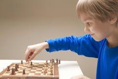 打一盘棋的微笑的孩子 免版税库存图片