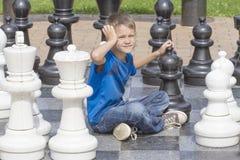 打下棋比赛和考虑他的接下来的步骤的男孩在一场室外下棋比赛期间使用与原物一样大小片断和委员会 免版税库存图片
