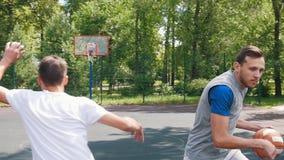 打与两个朋友的篮球和滴下单手的英俊的运动员 影视素材