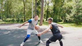 打与两个朋友的篮球,滴下球和投入它的英俊的运动员在篮子 股票视频