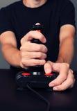 打与减速火箭的控制杆的游戏玩家电子游戏 免版税库存照片